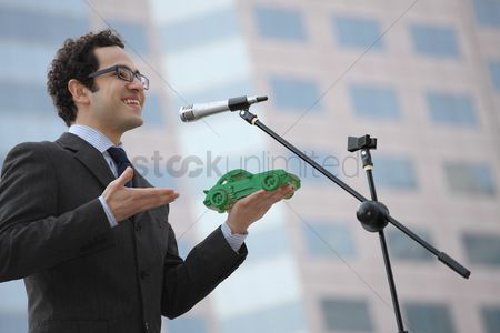 Business suit : Businessman holding a green car model while giving speech