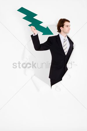 Cardboard cutout : Businessman holding an arrow pointing down