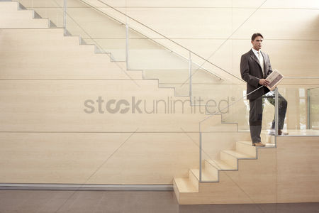 Stairs : Businessman holding newspaper standing on stairs