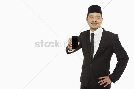 Portability : Businessman holding up a mobile phone
