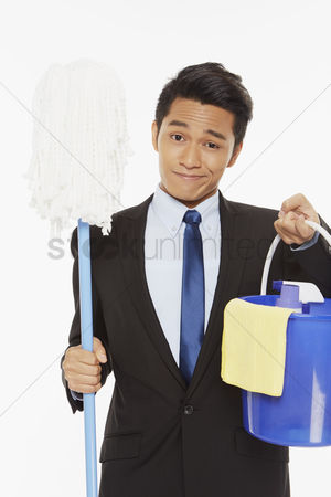Business suit : Businessman holding up a mop and other cleaning supplies