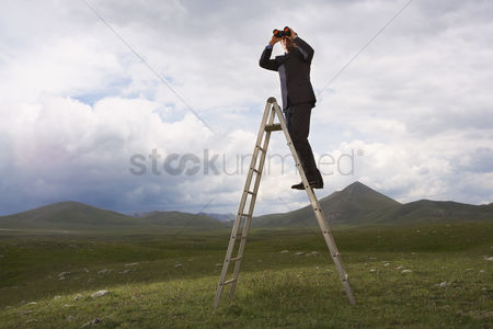 Moody : Businessman in mountain field on ladder looking through binoculars low angle view