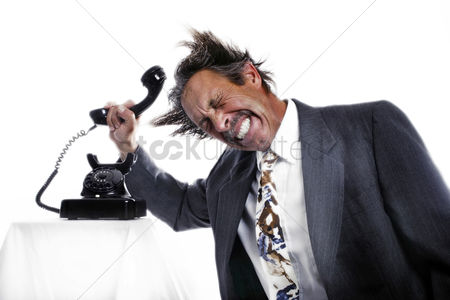 Business suit : Businessman knocking his head with a phone receiver