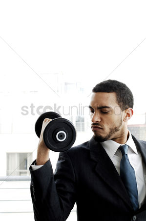 Strong : Businessman lifting dumbbell