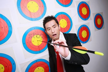 Amazed : Businessman looking at arrow on bull s-eye of target