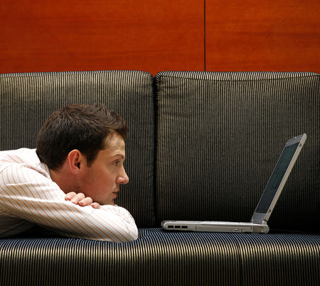 Enjoying : Businessman lying on the couch using laptop