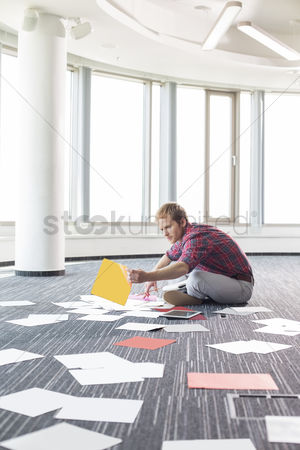 Collection : Businessman organizing photographs while sitting on floor at creative office