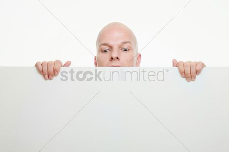 Bald : Businessman peeking from behind white placard