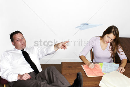 Attitude : Businessman playing with paper plane while his colleague is busy working