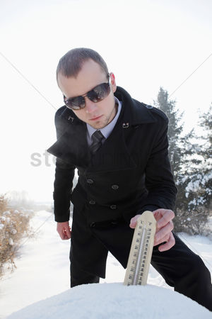 Thermometer : Businessman putting thermometer on snow