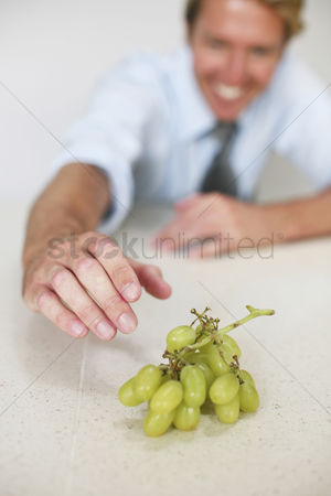 Grapes : Businessman reaching for grapes