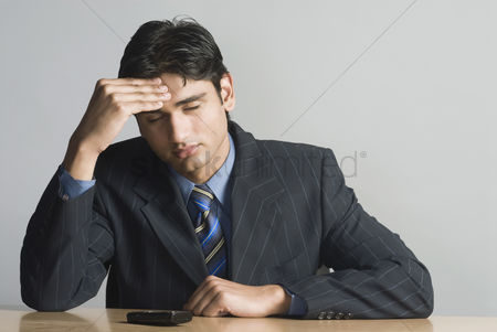 Corporation : Businessman rubbing his forehead
