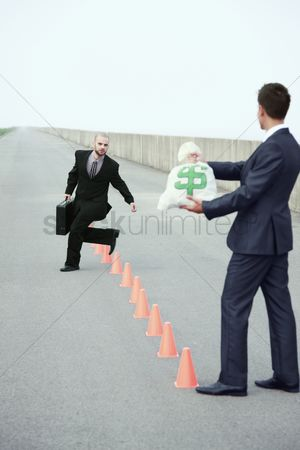 On the road : Businessman running in between traffic cones  another businessman holding a bag of money