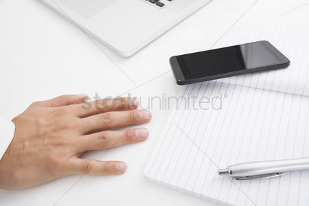 Pen : Businessman s hand on desk by cell phone pen and book
