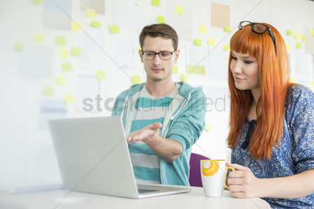 Internet : Businessman showing something to female colleague on laptop in creative office