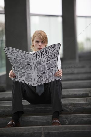 Cardboard cutout : Businessman sitting on the stairs reading newspaper