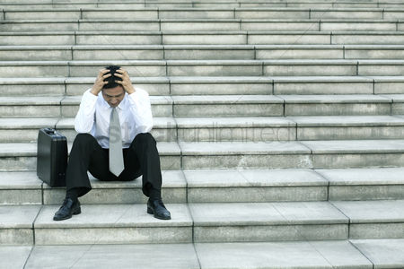 Asian : Businessman sitting on the stairs with his hands on the head
