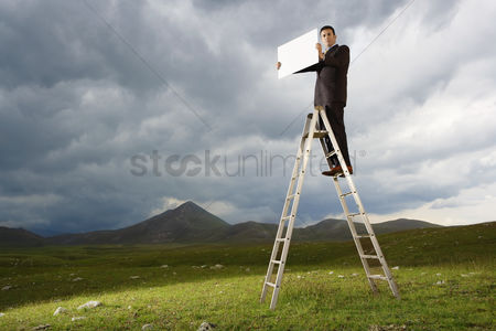 Moody : Businessman standing on a ladder in mountain field holding sign