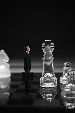Black background : Businessman standing with giant sized chess pieces