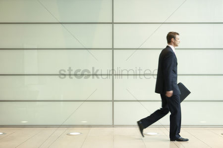 Determined : Businessman striding down office corridor side view