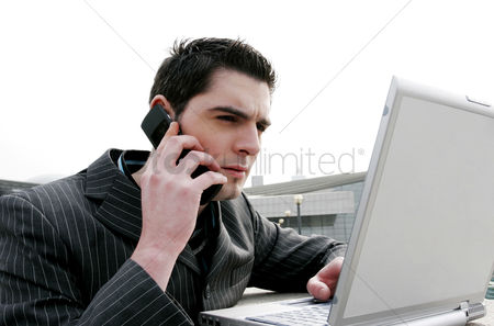 Employment issue : Businessman talking on the phone while using laptop