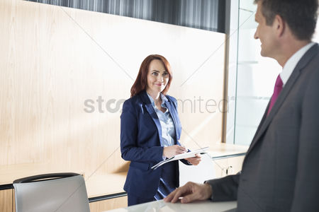 Notepad : Businessman talking with receptionist in office