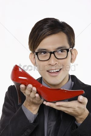 Man suit fashion : Businessman thinking while holding red stiletto shoe