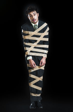 Forbidden : Businessman tied up with adhesive tape and looking sad
