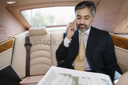 Car : Businessman using cell phone in private car