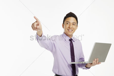Masculinity : Businessman using laptop and pointing to the right