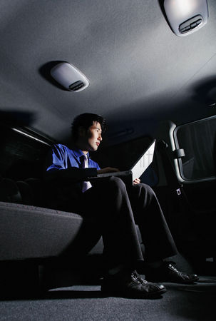 Spacious : Businessman using laptop in the car
