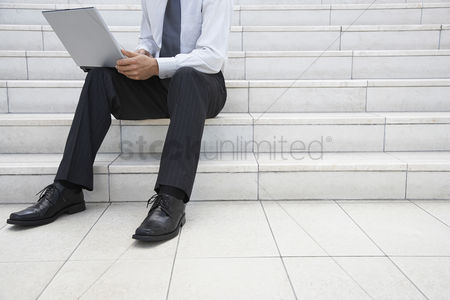 Steps : Businessman using laptop on steps outdoors low section