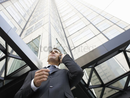 Cell phone : Businessman using mobile phone outside office  low angle view