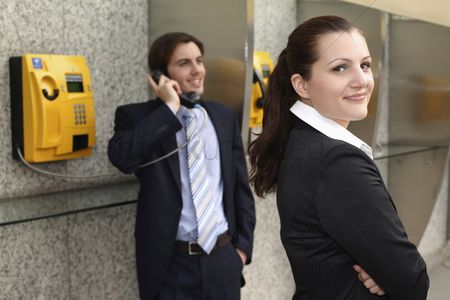 Pocket : Businessman using public telephone  businesswoman waiting at the side