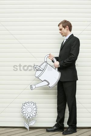 Cardboard cutout : Businessman watering flower