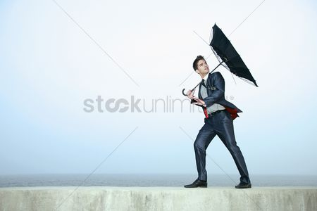 Color image : Businessman with an umbrella  wind blowing his umbrella away