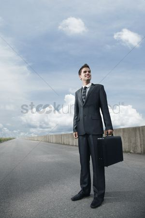 Motivation business : Businessman with bag standing on an empty road