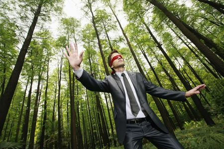 Three quarter length : Businessman with blindfold walking aimlessly in the forest