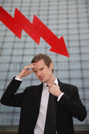 Cardboard cutout : Businessman with hand on forehead and arrow pointing down in the background