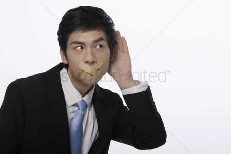Forbidden : Businessman with his mouth taped  trying to listen to a conversation