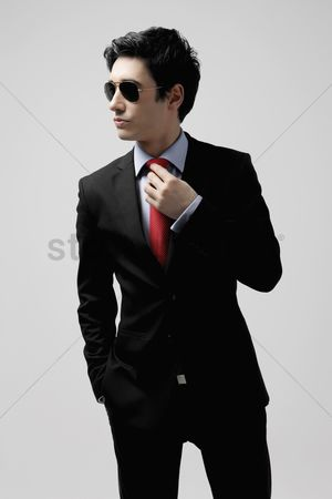 Man suit fashion : Businessman with sunglasses adjusting his tie