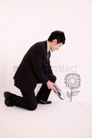 Cardboard cutout : Businessman with trowel kneeling beside plant