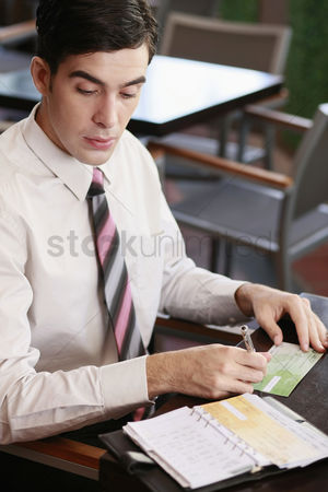 Spending money : Businessman writing on check