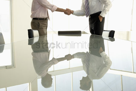 Mid adult man : Businessmen shaking hands by conference table mid section