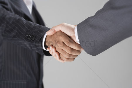 Relationship : Businessmen shaking hands mid-section