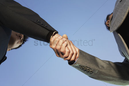 Strong : Businessmen shaking hands view from below