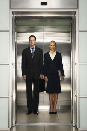 Selection : Businesspeople side by side in elevator portrait front view