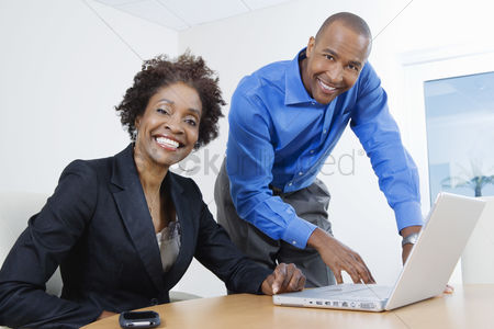 Posed : Businesspeople using laptop