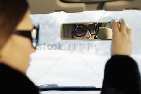 Car : Businesswoman adjusting car s rear view mirror