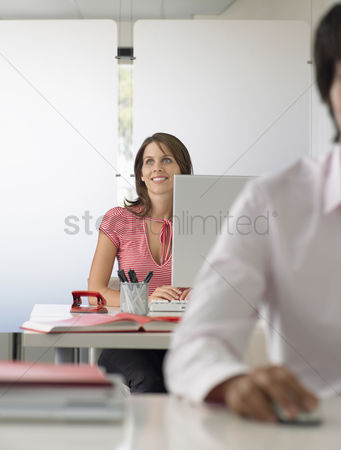 Interior background : Businesswoman at desk half length